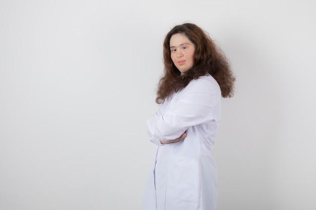 Retrato de uma jovem com síndrome de down em pé com os braços cruzados.