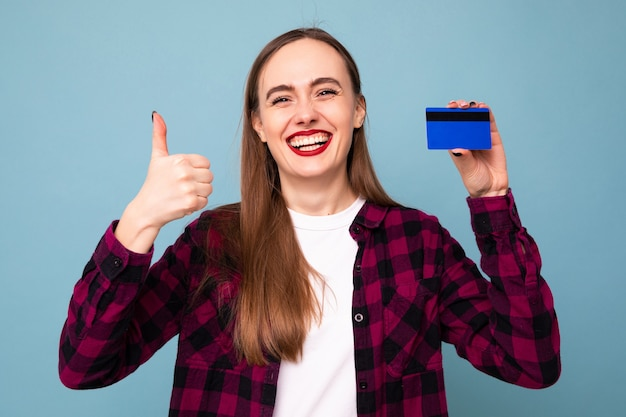 Retrato de uma jovem com um cartão de banco em um fundo azul