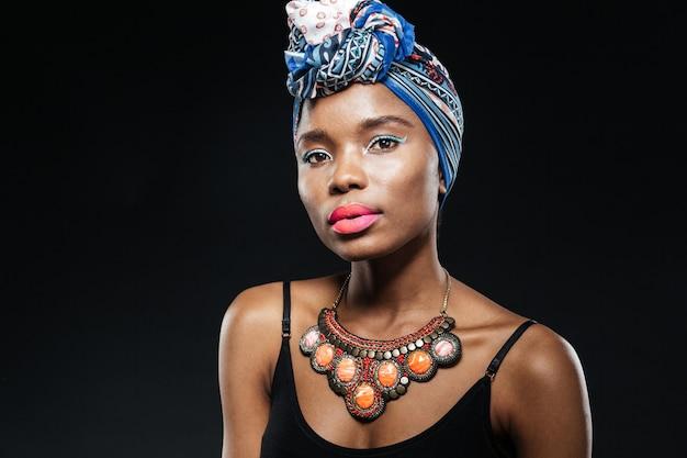 Retrato de uma jovem com um lenço de cabeça azul isolado na parede preta