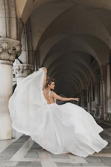 Retrato de uma jovem com um lindo vestido branco em uma arcada perto da praça de são marcos
