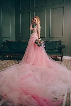 Retrato de uma jovem com um vestido rosa, segurando um buquê nas mãos contra um fundo interior vintage