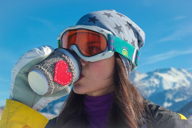 Retrato de uma jovem com uma máscara de esqui com um copo de papel. com coração vermelho na mão no fundo das montanhas de inverno e o céu azul.