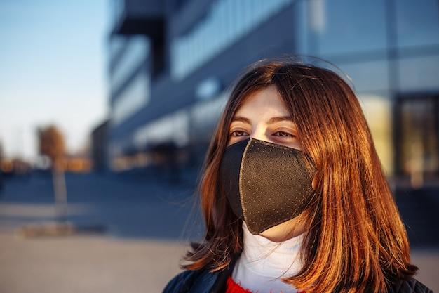 Retrato de uma jovem com uma máscara estéril médica preta, protegendo-se do coronavírus.