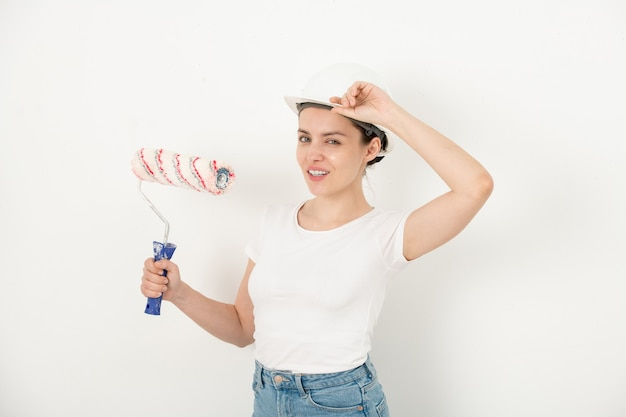 Retrato de uma jovem confiante e positiva ajustando o capacete de segurança e segurando o rolo de tinta contra a parede branca