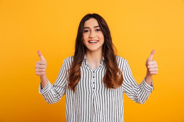 Retrato de uma jovem confiante, mostrando dois polegares para cima