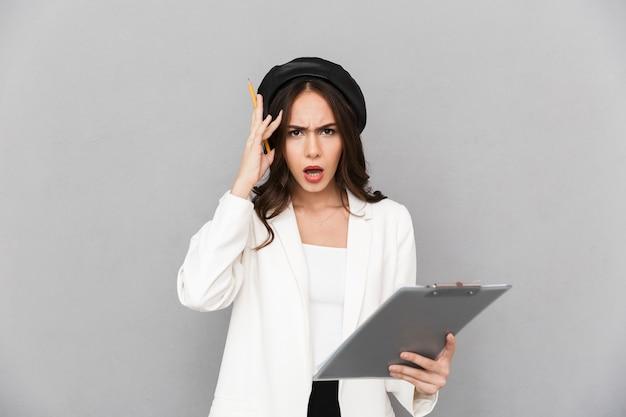 Retrato de uma jovem confusa, vestida com uma jaqueta, em pé sobre um fundo cinza, segurando o tablet