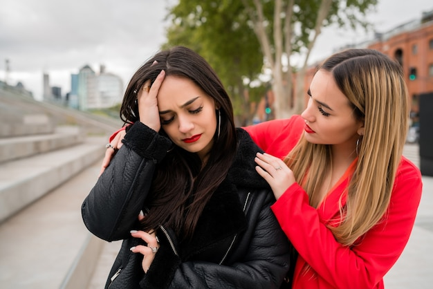 Retrato de uma jovem consolando e confortando sua amiga chateada enquanto está sentado ao ar livre na rua. conceito de amizade.