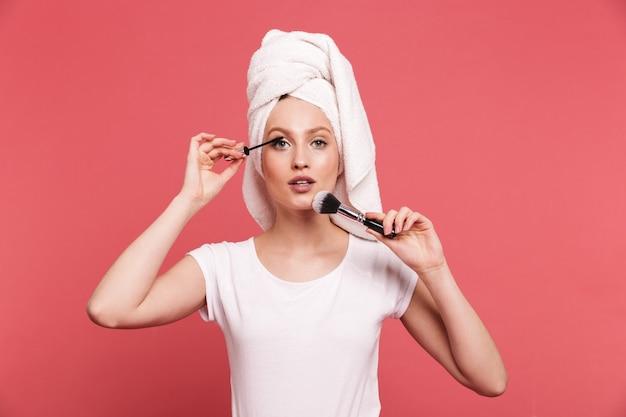 Retrato de uma jovem contente enrolada em uma toalha branca após o banho, aplicando cosméticos com um pincel de maquiagem isolado sobre a parede rosa