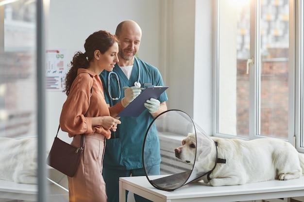 Retrato de uma jovem conversando com o veterinário na clínica veterinária com um cachorro usando uma coleira protetora na mesa de exame, copie o espaço