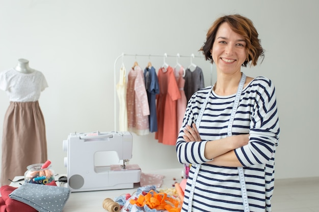 Retrato de uma jovem costureira positiva em pé na parede de sua mesa