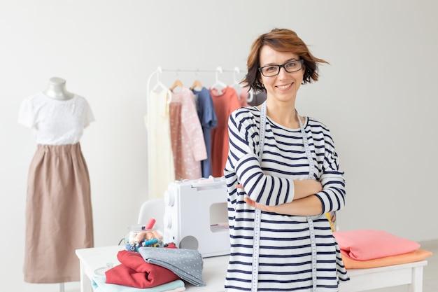Retrato de uma jovem costureira positiva em pé no fundo de sua área de trabalho
