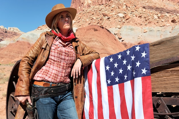 Retrato de uma jovem cowgirl loira com bandeira americana Foto Premium