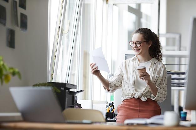 Retrato de uma jovem criativa olhando para as fotografias impressas e sorrindo durante a pausa para o café no interior de um escritório moderno, copie o espaço