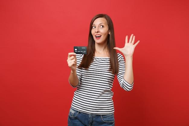 Retrato de uma jovem curiosa com roupas listradas, olhando para cima, segurando o cartão de crédito, mostrando a palma da mão isolada no fundo da parede vermelha brilhante. emoções sinceras de pessoas, conceito de estilo de vida. simule o espaço da cópia.