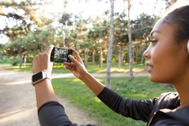 Retrato de uma jovem de 20 anos vestindo um agasalho esportivo preto e fones de ouvido, tirando uma foto de selfie no celular enquanto caminha pelo parque verde