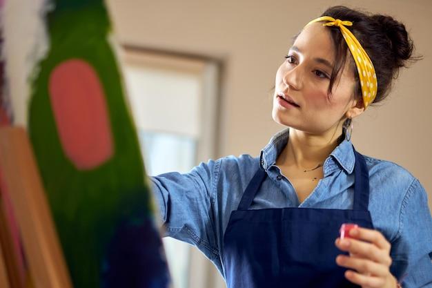 Retrato de uma jovem de avental inspirada enquanto trabalhava na pintura abstrata no acolhedor