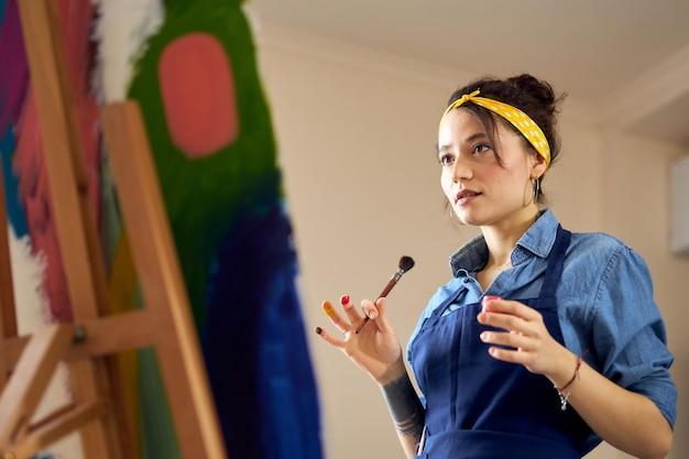 Retrato de uma jovem de avental segurando um pincel enquanto trabalhava na pintura abstrata no acolhedor
