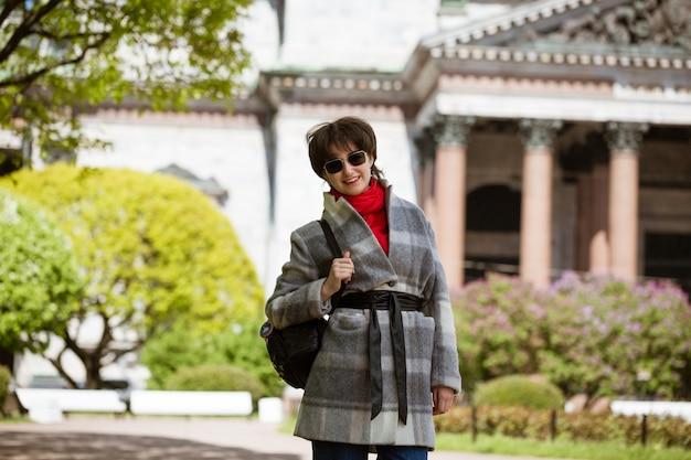 Retrato de uma jovem de óculos escuros com um casaco e uma mochila no contexto da catedral de santo isaac