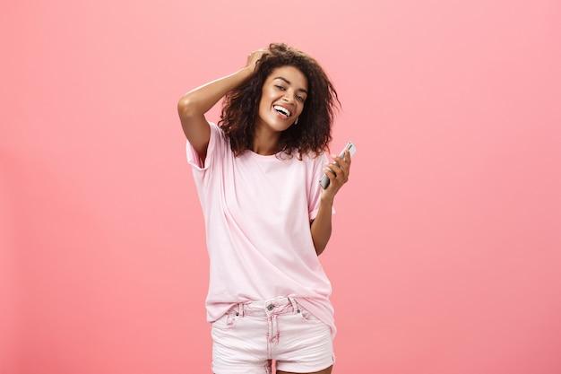 Retrato de uma jovem de pele escura, moderna e despreocupada, usando um smartphone, tocando o cabelo com alegria e olhando com um largo sorriso, segurando o celular posando contra a parede rosa