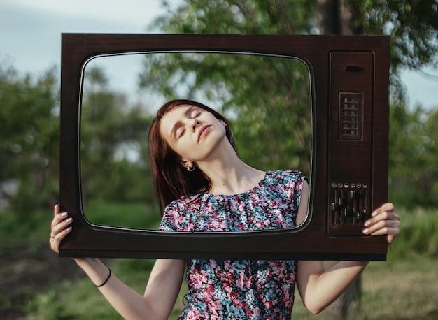 Retrato de uma jovem dentro de uma velha moldura de televisão retrô com os olhos fechados, problemas mentais de tecnologia e publicidade