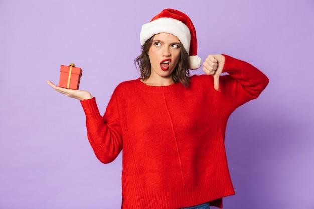 Retrato de uma jovem descontente com chapéu de natal, isolado na parede roxa, segurando uma caixa de presente surpresa.