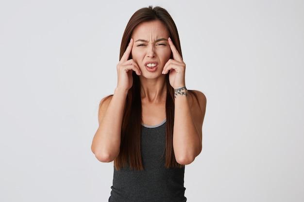 Retrato de uma jovem desesperada chateada com cabelo comprido tocando suas têmporas e sofrendo de dor de cabeça