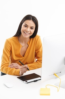 Retrato de uma jovem designer caucasiana usando um computador tablet gráfico e uma caneta stylus enquanto trabalhava em um escritório bem iluminado