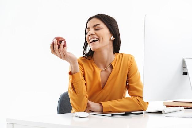 Retrato de uma jovem designer com um computador tablet gráfico segurando e comendo maçã enquanto trabalhava em um escritório luminoso