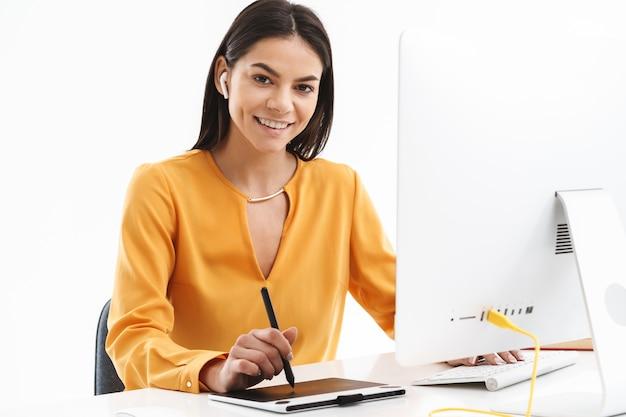 Retrato de uma jovem designer europeia usando um computador tablet gráfico e uma caneta stylus enquanto trabalhava em um escritório brilhante.