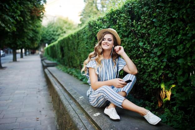 Retrato de uma jovem deslumbrante de macacão listrado, sentado no parque e ouvindo a música com os fones de ouvido.