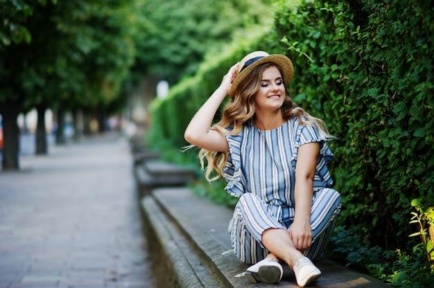 Retrato de uma jovem deslumbrante em macacão listrado sentado no parque.