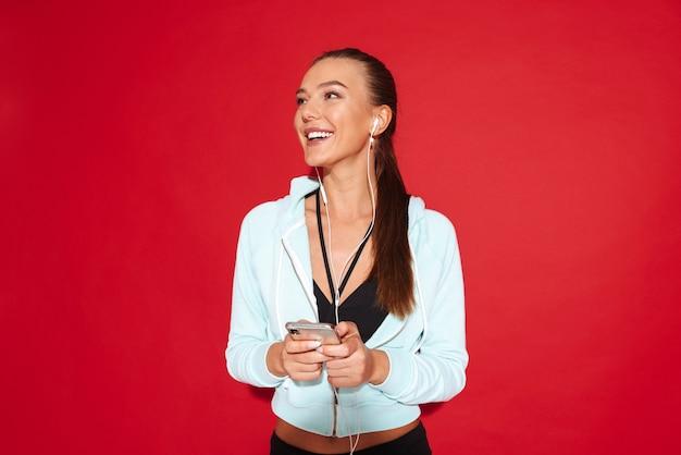 Retrato de uma jovem desportista em forma bonita, de pé, a ouvir música com auscultadores, a segurar num telemóvel