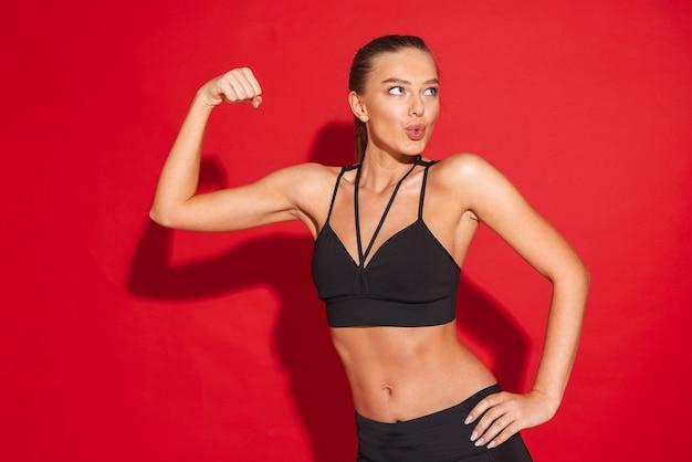 Retrato de uma jovem desportista em forma bonita, em pé, flexionando os bíceps