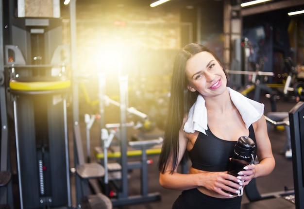 Retrato de uma jovem desportista sorridente alegre em roupas esportivas e toalha em volta do pescoço, garrafa de água na mão no ginásio. emoções positivas