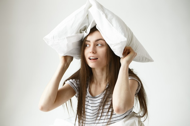 Retrato de uma jovem divertida e bonita jovem de 20 anos com cabelo escuro comprido e solto, vestindo uma camiseta listrada dentro de casa, olhando de soslaio com um sorriso misterioso, segurando um travesseiro branco sobre a cabeça