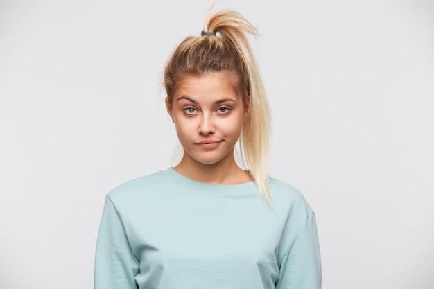 Retrato de uma jovem divertida e fofa com cabelo loiro e rabo de cavalo e camiseta azul
