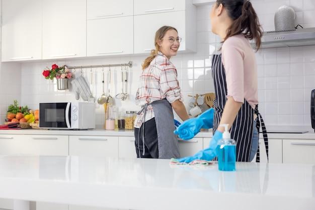 Retrato de uma jovem dona de casa alegre segurando material de limpeza