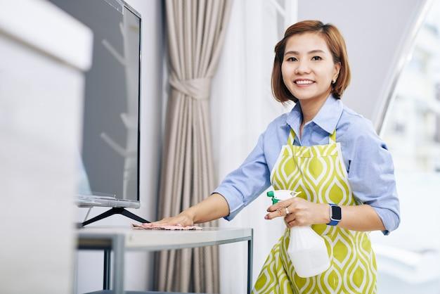 Retrato de uma jovem dona de casa asiática feliz limpando superfícies em apartamento com spray desinfetante