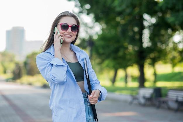 Retrato de uma jovem e atraente garota caucasiana com um laptop. mulher de negócios. conversa em um telefone celular. conceito freelance