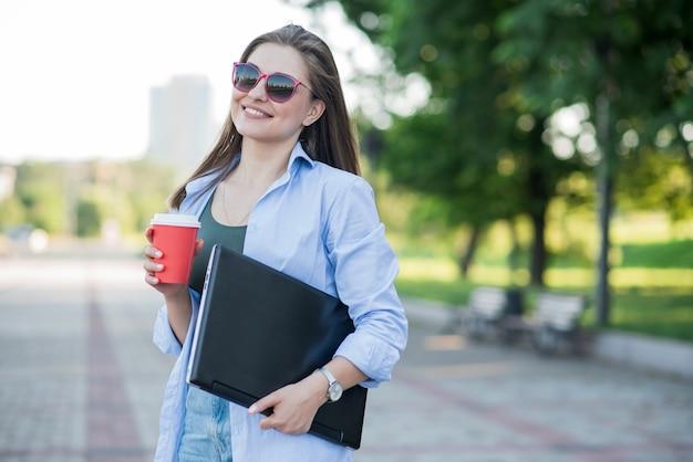 Retrato de uma jovem e atraente garota caucasiana. segurando um laptop e um café. empresária feliz