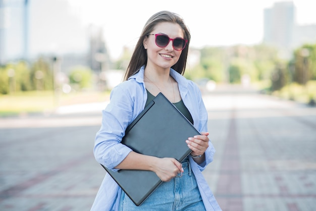 Retrato de uma jovem e atraente garota caucasiana. segurando um laptop. freelancer feliz