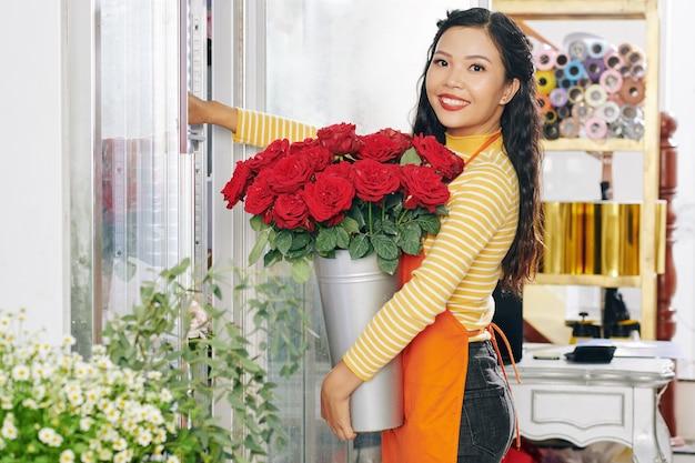 Retrato de uma jovem e bela florista vietnamita colocando um balde de rosas vermelhas frescas em uma exposição floral