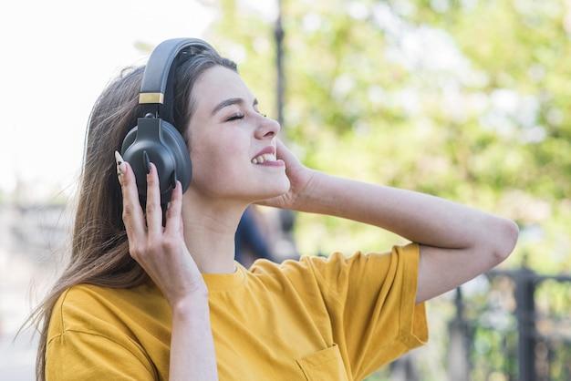 Retrato de uma jovem e bela garota caucasiana que escuta música com fones de ouvido