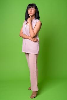 Retrato de uma jovem e bela mulher de negócios asiática contra uma parede verde