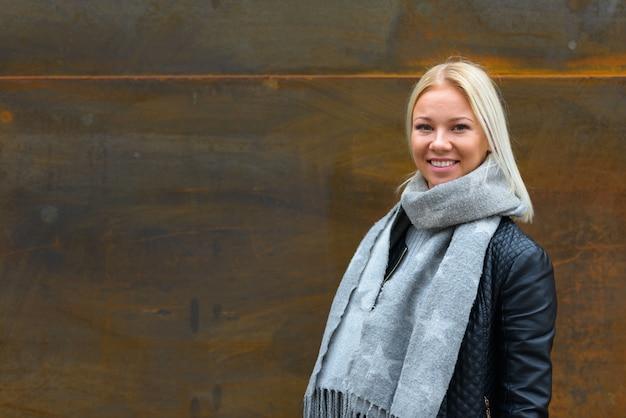 Retrato de uma jovem e bela mulher escandinava loira contra uma parede de metal enferrujada ao ar livre