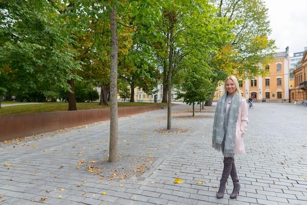 Retrato de uma jovem e bela mulher escandinava loira em uma praça tranquila na cidade ao ar livre