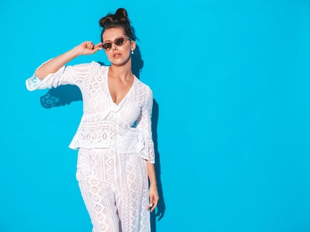 Retrato de uma jovem e bela mulher sexy com penteado ghoul. menina na moda hipster casual verão branco terno roupas em óculos de sol. modelo quente isolado em azul