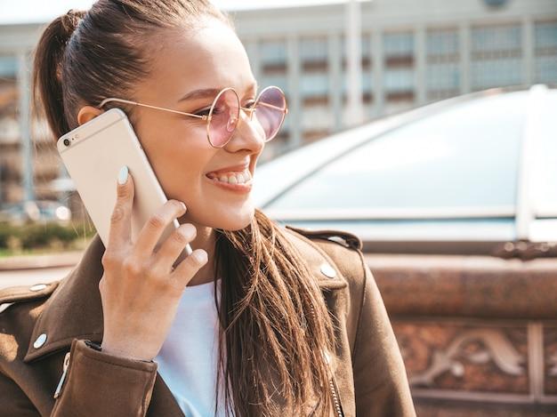 Retrato de uma jovem e bela mulher sorridente, falando no telefone menina na moda em roupas de verão casual engraçado e positivo feminino posando na rua