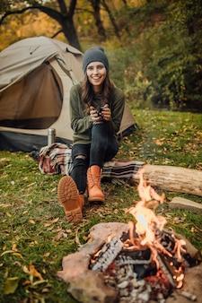 Retrato de uma jovem e bela turista feminina sentada no tronco na floresta perto da barraca e do saco de dormir