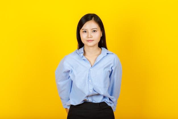 Retrato de uma jovem e bonita mulher de estilo chinês e japonês posar para a câmera com um gesto positivo e um sorriso amigável na câmera amarela.